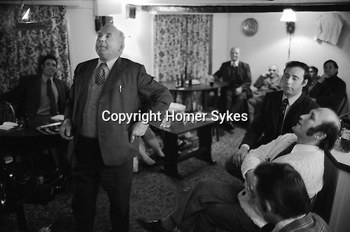 Stowell Court and Candle Auction, Tatworth, Somerset, England 1975. Auction takes place in lounge bar of the Poppe Inn.<br /> <br /> Mr Lloyd E Staples, local farmer and landowner, there is a road in the village named after him checks the candle, no one bidding is allowed to leave their seats.