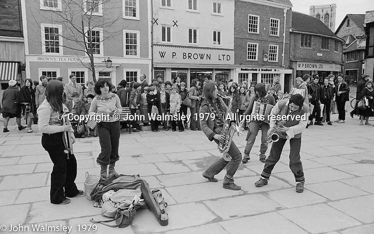 The York Street Band playing in York, March 1979.  Dena Attar on saxophone, Sarah Kemp on washboard, then the three members of the YSB: Sarha Moore (percussion), Anthea Gomez (accordian) and Ros Davies (saxophone).  Sarha Moore and Ros Davies went on to play in The Bollywood Band, and Ros also joined the Grand Union Band, in London.  Anthea Gomez went on to write and play music for the theatre and then BBC Drama before changing direction.