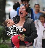 BOGOTA -COLOMBIA. 29-04-2014. Una mujer con  su hija grita desesperada por el efecto de los gases lacrimogenos que se entraron en su casa durante los disturbios en la Universidad Nacional.       Por varias horas encapuchados  lanzaron piedras , bombas papa y molotov contra la Policia Nacional en apoyo al paro agrario.  /A woman with her daughter screams desperate for the effects of tear gas that entered his house during the riots at the National University. For several hours hoods threw stones, Molotov bombs and potatoes against the National Police to support the agricultural strike.. Photo: VizzorImage/ Felipe Caicedo / Staff