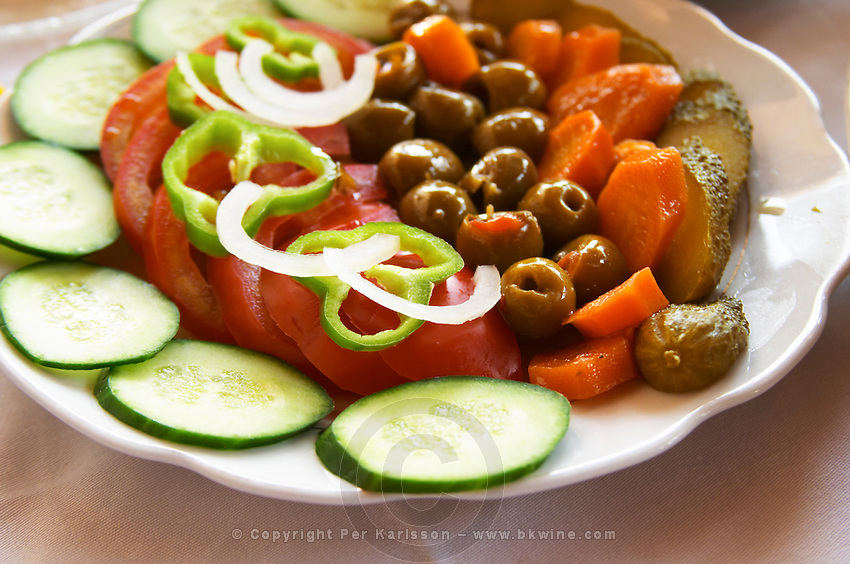 Salad with tomatoes, onions, green bell peppers, cucumbers, cornichons olives and carrots. Berat lower town. Albania, Balkan, Europe.