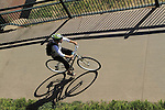 Man biking on bike path in Confluence Park, Denver, Colorado. .  John offers private photo tours in Denver, Boulder and throughout Colorado. Year-round.