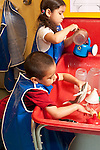 Education Preschool 3-4 year olds boy and girl playing separately at water table. wearing smocks