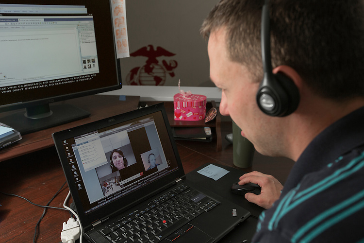 Mathew speaks with Jimena Romera from Buenos Aires during a monthly team conference call. Working for Ernst & Young, Mathew is able to work from home giving him more time to spend with this family and to help out around the house.