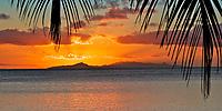 Sunset on Taha'a and Raiatea islands, with palm tree leaves on Huahine island, a romantic honeymoon destination near Tahiti, Polynesia, Pacific Ocean
