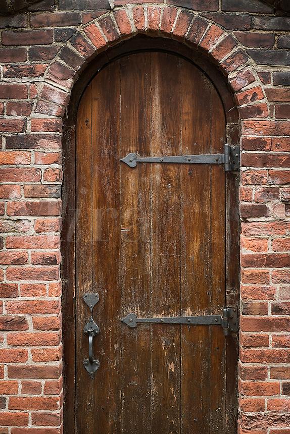 Arched rustic wooden door and walled garden.