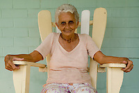 Portrait of a senior Cuban woman sitting on an adirondack chair on her porch, Vinales, Pinar del Rio Province, Cuba.