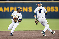Michigan Wolverines second baseman Ako Thomas (4) fields a ground ball as teammate Jack Blomgren (18) looks on against the Maryland Terrapins on April 13, 2018 in a Big Ten NCAA baseball game at Ray Fisher Stadium in Ann Arbor, Michigan. Michigan defeated Maryland 10-4. (Andrew Woolley/Four Seam Images)