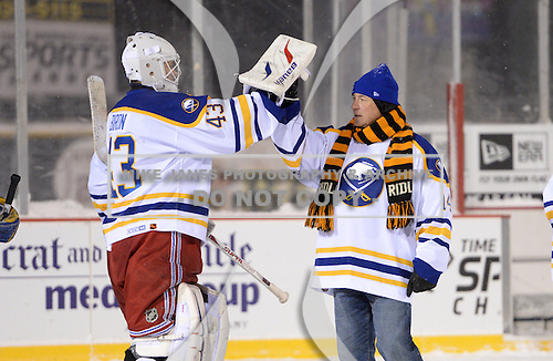 Honorary Coach Rene Robert (14) and Martin Biron (43) greet each other after The Frozen Frontier Buffalo Sabres vs. Rochester Amerks Alumni Game at Frontier Field on December 15, 2013 in Rochester, New York.  (Copyright Mike Janes Photography)