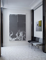 A simple seating area in the entrance hall, which has a marble terrazzo floor and corner columns of nickel-trimmed rosewood. Three fixed chairs are upholstered in fabric in different shades of grey and contemporary artworks are displayed on the walls.