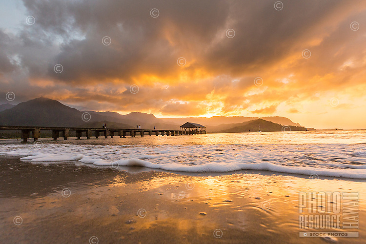 At sunset, a small wave washes in to Hanalei Bay Beach, with the Hanalei Pier to the left, Kaua'i.
