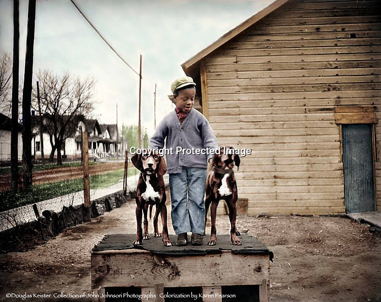 """BOY WITH HOUNDS<br /> To pose this pair of fine hounds atop their doghouse, the photographer has enlisted the services of a boy in a crooked-buttoned cardigan sweater. Some of the most captivating photographs are those where children are center-stage. In spite of their often tattered clothing, children are never depicted as downtrodden or """"less than"""". Rather, they have a special nobility."""