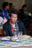 Myanmar, Burma.  Burmese Man Having Refreshments in a Roadside Coffee Shop, Shan State.