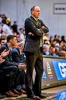 16 March 2019: University of Vermont Catamount Head Coach John Becker watches his team play against the UMBC Retrievers in the America East Championship Game at Patrick Gymnasium in Burlington, Vermont. The Catamounts defeated the Retrievers 66-49, avenging their loss against the same team in last years' Championship Game. Mandatory Credit: Ed Wolfstein Photo *** RAW (NEF) Image File Available ***