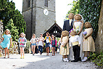 Scarecrow Festival at Kettlewell in Yorkshire 2013<br /> <br /> Local church has wedding group at the entrance.<br /> <br /> Scarecrows are made by local community and places in and around their front gardens.  Competition is fierce but it's all to raise money  for the local church  and other local projects to benefit the whole community.<br /> <br /> <br /> <br /> Picture by Gavin Rodgers/ Pixel 8000 <br /> <br /> 07917221968