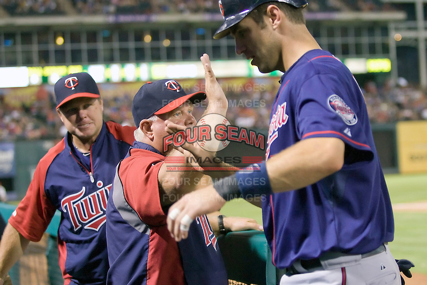 Minnesota Twins catcher Joe Mauer #7 is greeted in the dugout by manager Ron Gardenhire after scoring a ninth inning run in the Major League Baseball game against the Texas Rangers at the Rangers Ballpark in Arlington, Texas on July 27, 2011. Minnesota defeated Texas 7-2.  (Andrew Woolley/Four Seam Images)