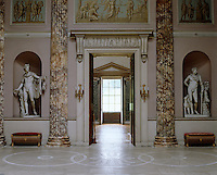 A pair of classical sculptures flank a doorway in the Marble Hall which was designed by Robert Adam
