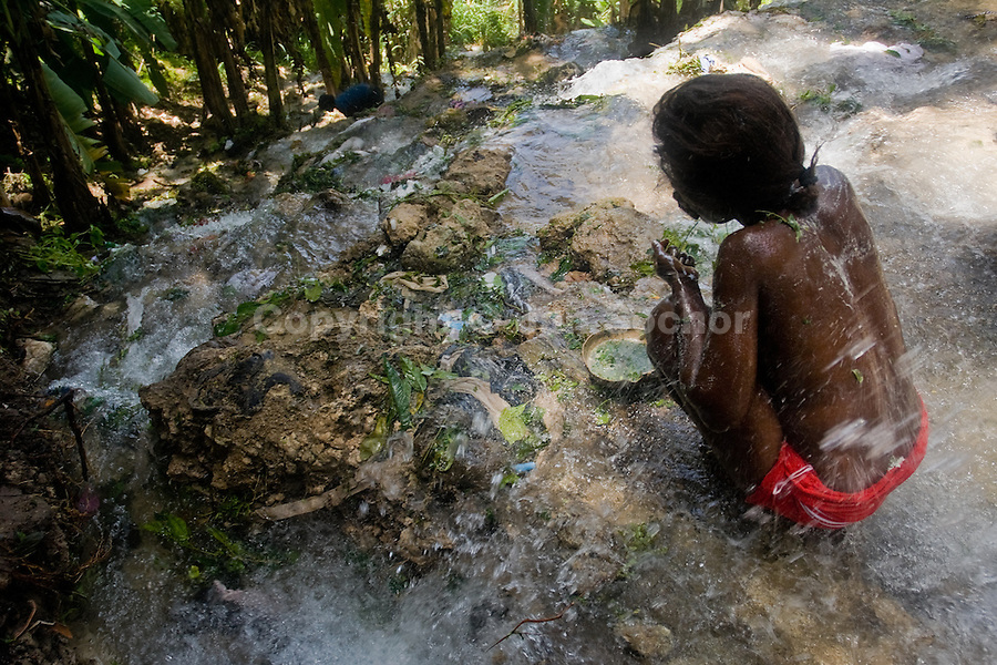 A Haitian woman performs a bathing and cleaning ritual, using the aromatic herbs, under the waterfall during the annual religious pilgrimage in Saut d'Eau, Haiti, July 16, 2008. Every year in summer thousands of pilgrims from all over Haiti make the religious journey to the Saut d'Eau waterfall (100km north of Port-au-Prince). It is believed that 150 years ago the spirit of Virgin Mary (Our Lady of Mount Carmel) has appeared on a palm tree close to the waterfall. This place became a main pilgrimage site in Haiti since then. Haitians wearing only underwear perform a bathing and cleaning ritual under the 100-foot-high waterfall. Voodoo followers (many Haitians practise both voodoo and catholicism) hope that Erzulie Dantor, the Voodoo spirit of water, manifest itself and they get possessed for a short moment, touched by her presence.