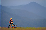 young woman riding bicycle in mountains