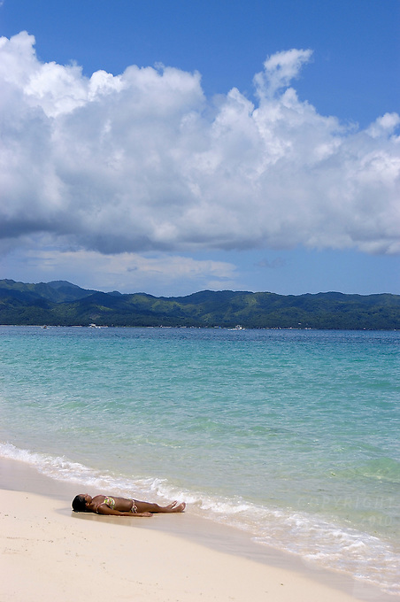 A tourist, girl sunbathing on the famous white beach on the island of Boracay, Philippines