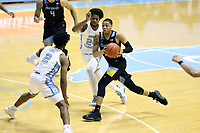 CHAPEL HILL, NC - FEBRUARY 24: Greg Elliott #5 of Marquette is defended by Kerwin Walton #24 and Caleb Love #2 of North Carolina during a game between Marquette and North Carolina at Dean E. Smith Center on February 24, 2021 in Chapel Hill, North Carolina.