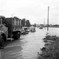 14 septembre 1963. Scène d'inondation : vue d'ensemble camions de la ville de Toulouse escortant plusieurs véhicules à travers les eaux