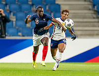 LE HAVRE, FRANCE - APRIL 13: Viviane Asseyi #18 of France fights for the ball with Crystal Dunn #19 of the USWNT during a game between France and USWNT at Stade Oceane on April 13, 2021 in Le Havre, France.