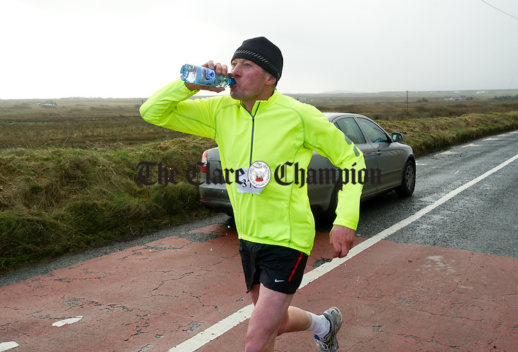 John O Connell gets in so,me refreshment on the go during the West Clare Mini Marathon from Carrigaholt to Kilkee. Photograph by John Kelly.