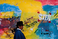 """A man passes in front of a colorfully paited wall during the Inti Raymi fiesta in Pichincha province, Ecuador, 26 June 2010. Inti Raymi, """"Festival of the Sun"""" in Quechua language, is an ancient spiritual ceremony held in the Indian regions of the Andes, mainly in Ecuador and Peru. The lively celebration, set by the winter solstice, goes on for various days. The highland Indians, wearing beautiful costumes, dance, drink and sing with no rest. Colorful processions in honor of the God Inti (Sun) pass through the mountain villages giving thanks for the harvest and expressing their deep relation to the Mother Earth (Pachamama)."""