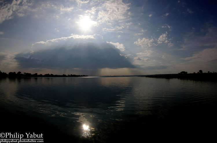 A not-so-distant thunderstorm reflects off the Zambezi River.
