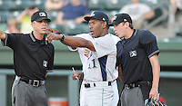 Manager Ivan De Jesus (11) of the Lexington Legends checks the ground rules with umpires Mike Patterson, left, and Alex Ziegler prior to a game against the Greenville Drive on May 2, 2012, at Fluor Field at the West End in Greenville, South Carolina. Lexington won, 4-2. (Tom Priddy/Four Seam Images)