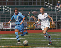 Boston Aztec forward Lucy Gildein (27) on the attack.  In a Women's Premier Soccer League (WPSL) match, Boston Aztec (white) defeated Seacoast United Mariners (blue), 2-1, at North Reading High School Stadium on Arthur J. Kenney Athletic Field on on June 23, 2013. Due to injuries through the season, Seacoast United Mariners could only field 10 players.