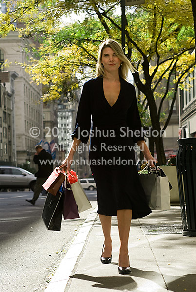 Young blonde woman carrying gift bags walking down the sidewalk