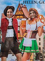 Tourists pose in German Octoberfest motif cut-out, Helen, Georgia, USA.