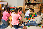 Education preschool 3-4 year olds groups of girls and boys playing separately, girls at dollhouse and boys building with colored plastic Duplo bricks