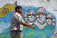 A Palestinian man passes by graffiti of militants of the Fattah faction, The Martyrs of Al Aqsa brigades, outside the Al Quds University in Gaza City. Photo by Quique Kierszenbaum