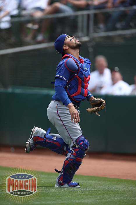 OAKLAND, CA - MAY 15:  Robinson Chirinos #61 of the Texas Rangers chases a foul ball against the Oakland Athletics during the game at O.co Coliseum on Wednesday May 15, 2013 in Oakland, California. Photo by Brad Mangin