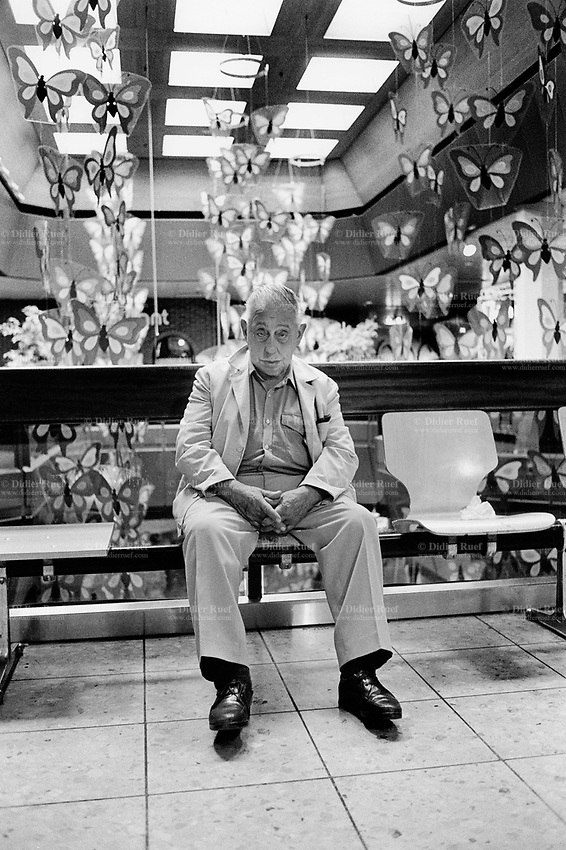 Switzerland. Canton Zürich. Winterthur. An old man half asleep sits alone on a chair in a shopping center. Plastic fake butterflies are hanged from the ceiling and used as decorations. Butterflies are insects in the macrolepidopteran clade Rhopalocera from the order Lepidoptera, which also includes moths. Adult butterflies have large, often brightly coloured wings, and conspicuous, fluttering flight. © 1990 Didier Ruef
