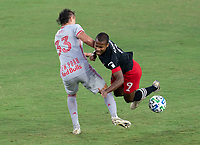 WASHINGTON, DC - SEPTEMBER 12: Aaron Long #33 of the New York Red Bulls tackles Ola Kamara #9 of D.C. United during a game between New York Red Bulls and D.C. United at Audi Field on September 12, 2020 in Washington, DC.