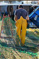 Young fisherman mending fishing nets, Palamos, Spain