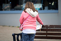 Pictured: A woman collects one of the envelopes left in various locations in Aberystwyth, Wales, UK on Christmas Eve. Saturday 24 December 2016<br />