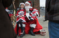 Santa Claus, portrayed by Santa Clarence, a member of the Amalgamated Order of Bearded Santas, poses for photos outside a shipping store where he greeted young and old to hear their Christmas wishes.