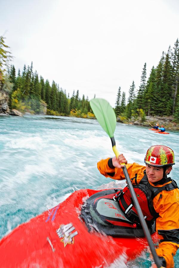 Andrew Jobe paddling whitewater kayak at the Widow Maker rapid on the Kananaskis River, Kananaskis County, Alberta, Canada