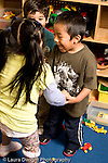 Education Preschool 3-4 year olds girl and boys playing in block area talking to each other animated conversation vertical