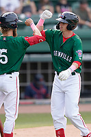 Nick Sogard (11) of the Greenville Drive gets an elbow bump from Cole Brannen (5) after hitting a home run in a game against the Bowling Green Hot Rods on Sunday, May 9, 2021, at Fluor Field at the West End in Greenville, South Carolina. (Tom Priddy/Four Seam Images)