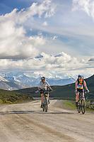 Women biking along the Denali Park Highway, Mount McKinley visible in the distance.