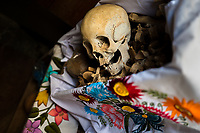 """A dried-up scull and bones are seen wrapped in an embroidered cloth and placed in a wooden crate inside a niche at the cemetery in Pomuch, Mexico, 26 October 2019. Every year on the Day of the Dead, people of Pomuch, a small Mayan community in the south of Mexico, visit the cemetery to take part in a pre-Hispanic tradition of cleaning of bones of their departed relatives (""""Limpia de huesos""""). People who die in Pomuch are firstly buried for three years in an above-ground tomb then the dried-up bodies are taken out, bones are separated, wrapped in a decorated cloth, put into a wooden crate, and placed on display among flowers for veneration."""