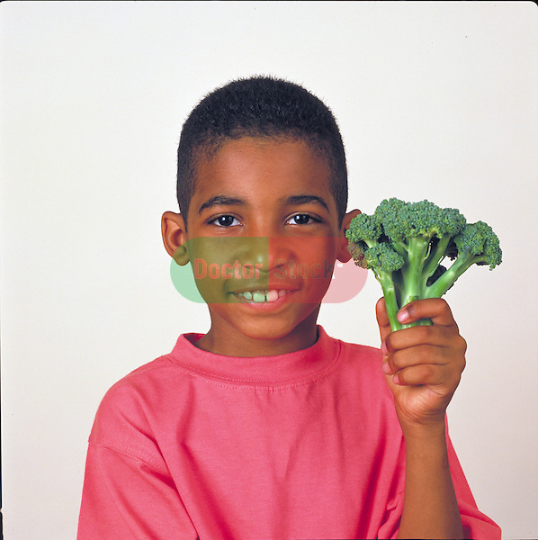 portrait of smiling young boy holding broccoli stalk