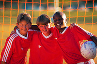 Three boys posing in soccer uniforms.