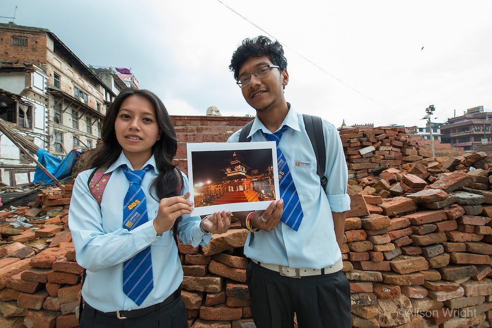 Nepal, Kathmandu, earthquake damage at Kathmandu Durbar Square. Students holding photos of how the temples looked previously.