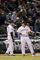 Charlotte Knights coach Ryan Newman (5) talks to Josh Phegley (4) as he stands on third base after hitting a triple against the Gwinnett Braves at BB&T Ballpark on April 16, 2014 in Charlotte, North Carolina.  The Braves defeated the Knights 7-2.  (Brian Westerholt/Four Seam Images)